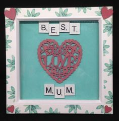 """White wooden scrabble letters saying """" Best Mum"""" with a wooden hand painted heart saying love. Frames are white, wooden with a leafy trim & wooden hand painted hearts on each corner. Scrabble Letters, Mothers Day Presents, Wooden Hand, Wooden Hearts, Gift Guide, Hand Painted, 3d, Personalized Items, Frame"""