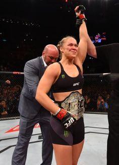 UFC president Dana White wraps the women's bantamweight championship belt around Ronda Rousey's waist. (Photo by Josh Hedges/Getty Images)