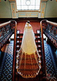 Werribee Park Mansion Wedding - Bride wearing a Beautiful Traditional Wedding Dress. Beautifully Long Laced trimmed wedding veil. Bride climbing the Mansions Italianate regal staircase. Absolutely Breathtaking!