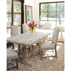 This handsome dining table is constructed of reclaimed pine wood with an antique white finish for a unique look. The distressed appearance of this dining table will add rustic appeal to any setting.