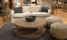 Round wood coffee table with round burlap poufs.