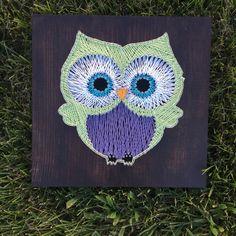création mignonne sur une planche de bois foncé à design petit hibou vert et violet aux grands yeux bleus