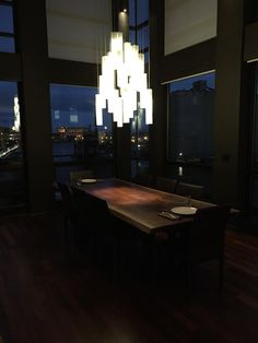 Our White candles chandelier over a modern dining table, with the background of a spectacular view at night time...so beautiful!!! #moderndiningchandelier #GalileeLighting #moderndiningchandelier #modernpendantlighting #chandelier #lighting #uniquelighting #beautifullighting #modernlightingMiami #customlightingMiami