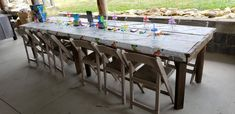 Rustic farm tables with dinosaur table cloth with crayons drink cups and bubbles