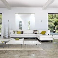 salon élégant avec un canapé blanc et tables basses en blanc et gris, coussins en vert anis, gris et blanc et plancher gris