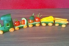 Saw this with halves of bell peppers - that way, more stuff fits and you can even include the dip in the train. Wheels of cucumber slices attached with pins or cream cheese. Can run on tracks drawn on paper plate.