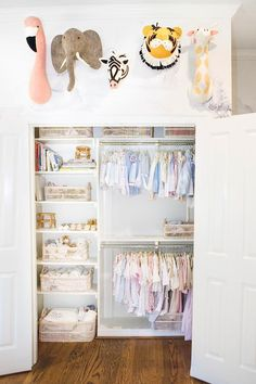Adorable felt animal heads are mounted on a white wall above a well stocked nursery closet boasting built in in shelves stocked with white bins positioned beside stacked clothing rails.