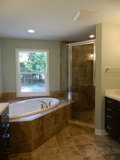 Tile flooring and tub deck with drop in bath tub. Framed corner shower with tiled walls and floors. Recessed lighting. Stained cabinetry with cultured marble countertops. Cased window.