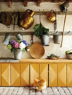 Love everything about this. Cobblestone-esque floor, rustic wood, white brick backsplash, mustard wood, beautiful hydrangea, baskets, and hanging utensils and watering cans. I'll even take the chicken.