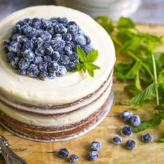 This moist and light vanilla naked cake is iced with tangy cream cheese icing and topped with sugared blueberries. It's rustic, sweet and simply delicious.