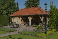 Eiken tuinhuis. Voorzien van rode dakpannen omgeven door een schitterende tuin.