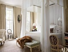 The Lairds' canopy bed is curtained in a Rogers & Goffigon fabric and dressed with embroidered linens by E. Braun & Co.; the couple picked up the inlaid wall bracket on a trip to Istanbul, and the handwoven abaca floor covering is by Beauvais Carpets | archdigest.com