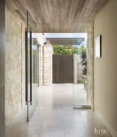 Split face limestone Entry featuring a pivoting frameless door made of tempered glass...