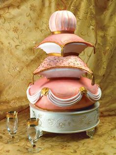 Sweetd Dreams    This cake, created by Susan Gambelli of Susan Gambelli Custom Cakes, is proof that dreams do come true! Four tiers of hand-sculpted pillows are covered in fondant in shades of coral and accented in gold. Decorated with a combination of painting, airbrushing, and filigree design, the cake is adorned with edible beads, tassels, swags, and decorative gold finials. The inside is just as rich: marble cake filled with milk chocolate caramel mousse and candied pecans. (Susan…