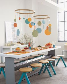 Graphic mobiles made from construction paper and embroidery hoops can serve as party decor as well as a take-home nursery decorations for any baby shower celebration.