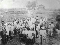 Hindoestaanse en Javaanse arbeiders wachten op uitbetaling op plantage Clevia in Commewijne anno 1905 Foto: Tropenmuseum.