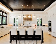 Beautiful white kitchen with dark wood.  Love the wood ceiling