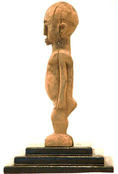 Country of origin: Burkina Faso  Measurement: 5x 5x 18x (cm)  Materials: Wood  Approximate Age: Mid 20th century  Overall Condition: Good  Damage, Repair: Some cracks due to old age  These Lobi figures were created to protect the people. The figure is not carved after a person, but after a spirit. They were usually placed on family altars. It protects the whole family from sickness and bad luck. It could also be used for divination and was past on from father to son.