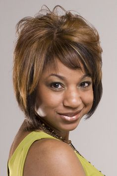 Short Hairstyle For Black Women, This woman has her hair layered throughout with bangs swept across on the forehead.