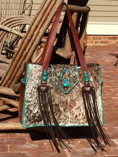A cowhide Buckaroo Diaper Tote with the owners brand on the flap in turquoise suede, straps with turquoise stones and fringe and side pockets lined in suede. From gowestdesigns.us