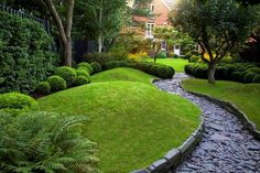 24 Beautiful Boxwood Garden Ideas Difference in textures is striking between the groomed lawn area and the rough path.