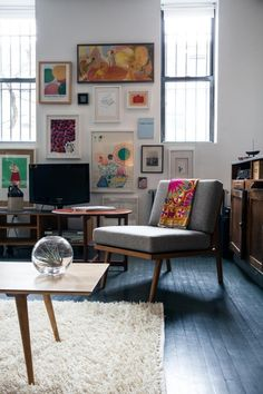 like the compilation of art hung on the wall, the gray upholstery of the danish modern chair, and the bright colored throw (brooklyn loft via remodelista)