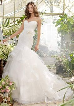 Gown features lace, elongated bodice, tiered skirt and horsehair trim. Matching horsehair belt available.