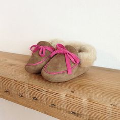Handmade baby moccasins from the North Cornish Coast. Natural sheepskin with pink trim.