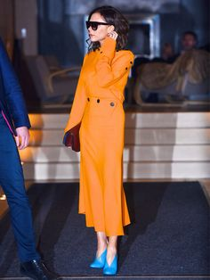 Victoria Beckham wearing orange dress with bright blue shoes and has just highlighted a key new colour combination for spring.