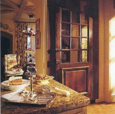 On either side of the entrance to the sitting area , old French exterior doors conceal kitchen necessities.