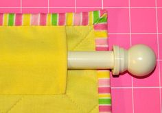 How to attach a hanging sleeve to your quilt.. A hanging sleeve is attached to the back of a quilt or wall hanging to house a rod or hanger. It is attached after the quilting is done but at the same time as you are binding your quilt. You will need to have finished Step 2 in our 'How to bind your quilt using stitched mitred corners' tutorial to be ready to attach the hanging sleeve.