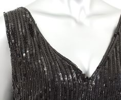 Sequined tulle dress, c.1925 The unstructured dress is comfortable and effortless to wear. The black rayon lining is attached around the neckline and armholes. The dress is cut straight to the hipline, where it is attached to a bias-cut circular skirt.  The sophisticated black-on-black design is punctuated with bursts of glitter from a textured assortment of sequins and beads: large diamond-shaped paillettes, sequins, and glass beads.   Detail 6