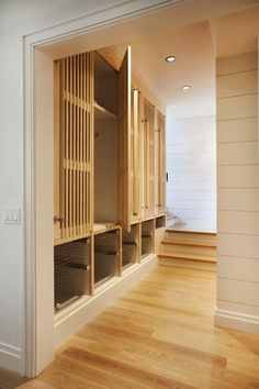 A staircase leads to a shiplap mudroom filled with built-in lockers finished with teak slat doors placed over a nook filled with stacked pull-out vintage metal bins. Wood Lockers, Small Lockers, Built In Lockers, Mudroom Cubbies, Vintage Lockers, Interior Design Layout, Timber Slats, Small Condo, Condo Remodel