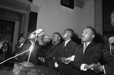 "In this March 9, 1965 file photo, Dr. Martin Luther King, Jr., joins hands with other African American leaders singing ""We Shall Overcome"" at a church rally in Selma, Ala."