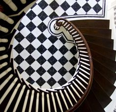 View of the stunning spiral staircase and black and white marble foyer floor in Carolyne Roehm's historic Greek Revival home in Charleston, SC.