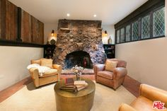 Fireside Feng Shui - One of the home's three stone fireplaces is flanked by two oversized leather armchairs. Cabin Fireplace, Fireplace Mantels, Stone Fireplaces, Hollywood Hills Homes, Outdoor Oven, Thing 1, Charli Xcx, Los Angeles Homes, House On A Hill