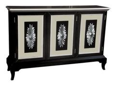 The versatility of this credenza makes it an ideal addition for multiple areas of the home. It makes a striking statement in a foyer or dining room with the additional bonus of storage area. A glossy black finish against white and tan door panels withdecorative sunburst motifs will bring contrast and drama to any space.