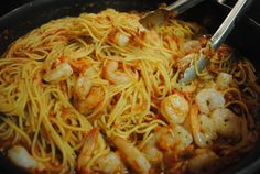 Shrimp Fra Diavolo  1 lb. spaghetti or angel hair noodles 1 lb. shrimp, peeled and deveined 4 Tbs. olive oil 5 cloves minced garlic 1 medium onion, finely chopped 1 cup dry white wine 1 28 oz. can crushed tomatoes 1 1/2 tsp. red pepper flakes 1/4 tsp. dried oregano 1 Tbs. dried parsley flakes 1/2 Tbs. dried basil Grated or shredded parm