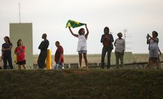 06-11-14_world_cup_25, A woman waves a Brazilian flag outside Itaquerao stadium, also known as Arena de Sao Paulo and Arena Corinthians, on June 8, 2014 in Sao Paulo, Brazil. Hundreds of fans turned up at the stadium to take a peek on the final Sunday before the opening of the 2014 FIFA World Cup match on June 12 between Brazil and Croatia.