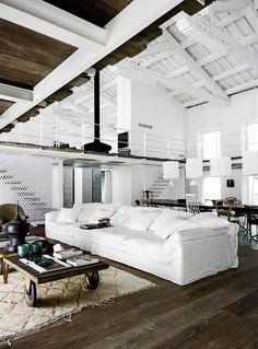 loft contemporain blanc aménagé avec un canapé blanc surdimensionné, une table basse industrielle et un tapis beige