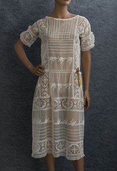 Embroidered tulle/filet lace dress , c.1924    The textural appeal of the wide bands of handmade filet lace is complemented by the raised embroidered flowers and rows of narrow tucks. The only other adornment is a small bouquet of ribbon flowers at the waist.  975