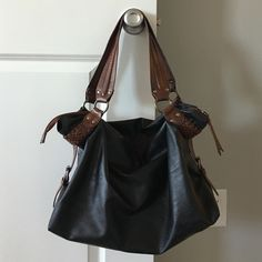 New York & Company tote Black and brown. Great bag. Zipper and lots of room inside. Brown straps on the bottom part have a braided effect which I personally love. Very chic and classic. A couple spots on the front but hardly noticeable. Pictures show them up close. Love this bag but I have too many! New York & Company Bags