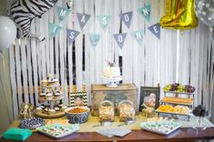 Baby boy first birthday party decor: safari theme food table, custom banner, zebra balloon, animal cookies, animal crackers