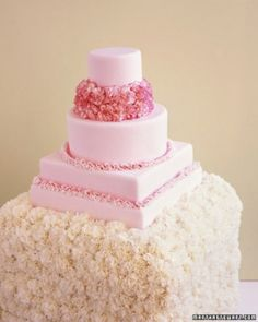 Pink Carnation Wedding Cake  A four-tier cake covered in pink fondant celebrates the beauty of carnations. Hundreds of them blanket the simple wooden box it rests on, an idea that works well with carnations because they are so affordable.