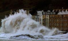 Waves crash against the Aberystwyth coastline, in Wales,