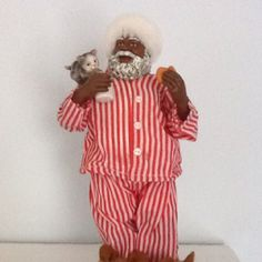 POSSIBLE DREAMS BLACK SANTA. He is dressed in his pajamas and is eating a cookie and drinking his glass of milk. Sitting on his shoulder is a cute little kitten. He is wearing his slippers and has a matching red & white strioed hat on.