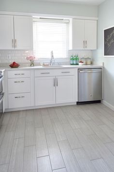 This bright kitchen makeover designed by Nicole Gibbons of So Haute is timeless & budget friendly. For subtle contrast, she incorporated soft gray tones in the flooring and countertops, in addition to a pale sage wall color.