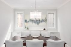 White and gray dining room features a crystal droplet drum pendant hanging over a cherry stained dining table lined with white dining chairs placed in front of a built-in buffet cabinet and blue abstract art flanked by windows.