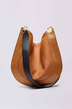 This modern crossbody satchel is an unexpected statement piece for every day. A luxurious calf hair body and soft leather border are accented with a contrast leather strap and half moon hardware. With zip top closure and detachable leather pouch. Leather Pouch, Leather Purses, Leather Crossbody, Leather Handbags, Leather Bags, Soft Leather, Brown Leather, Hobo Purses, Purses And Bags