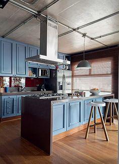 A cozinha deste triplex de 281 m² possui armário de madeira com inspiração londrina. No teto cinza, as instalações elétricas ficam aparentes.  Projeto do arquiteto Nelson Kabarite